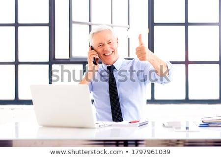 Smiling businessman giving thumbs up. Stock photo © lichtmeister