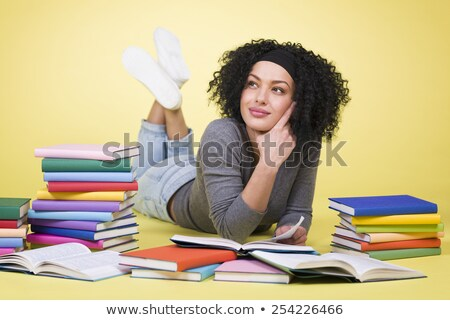 Joyous student girl reading surrounded by colorful books. Stock photo © lichtmeister
