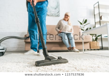 young woman vacuuming and senior woman sitting on sofa stock photo © photography33