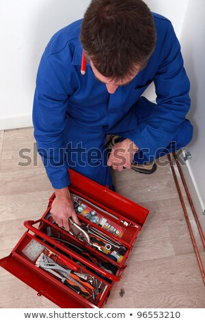 Artisan knelt by red tool box Stock photo © photography33