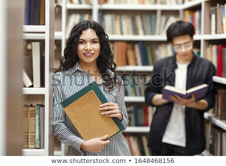 Stock photo: young woman in public library and guy in background