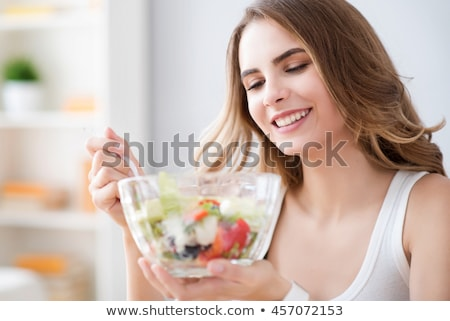 Delighted woman is eating a salad  Stock photo © wavebreak_media