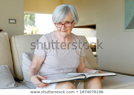 Pretty red-haired female reading a book while sitting on her bed Stock photo © wavebreak_media