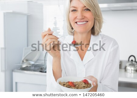 Stock photo: Happy mature woman with strawberry.
