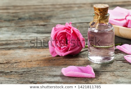 bottle with essence oil and rose flowers isolated on white Stock photo © tetkoren