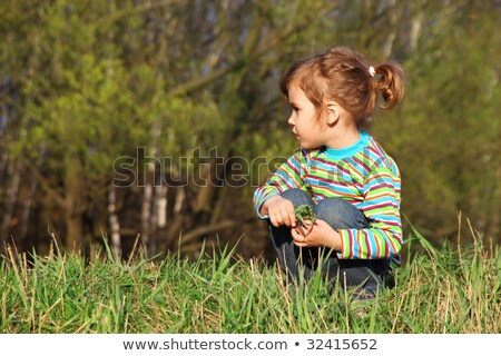 little girl with grass in hands sits on fringe of forest Stock photo © Paha_L
