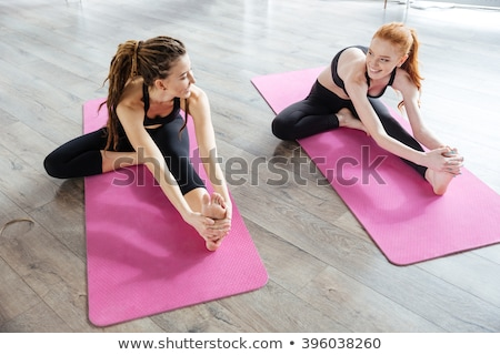 two beautiful women stretching legs in yoga center stock photo © deandrobot