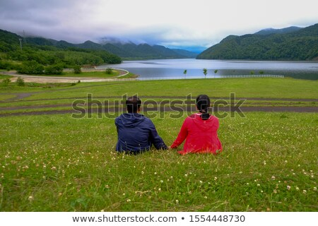 happy young man sitting on grass field Stock photo © feedough