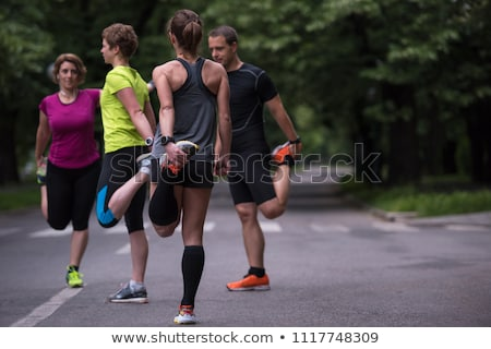Smiling runner warming up on the street stock photo © deandrobot