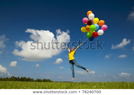 Smiling woman in field with balloons Stock photo © IS2