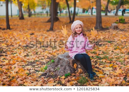 Stock photo: 5 years old girl standing by a tree