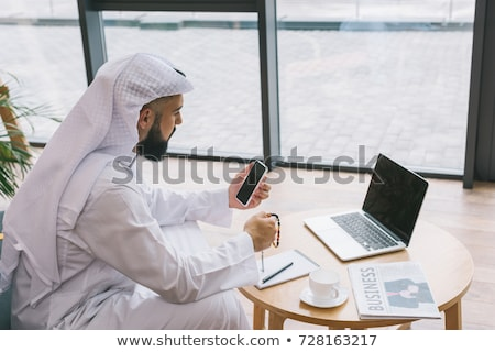 A Middle Eastern businessman sitting with a laptop Stock photo © monkey_business