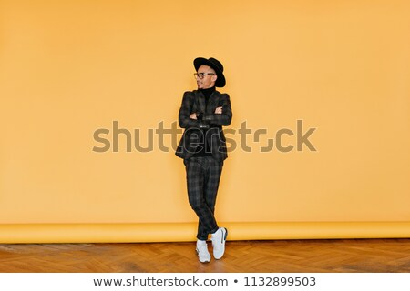relaxed elegant young man standing with legs crossed Stock photo © feedough