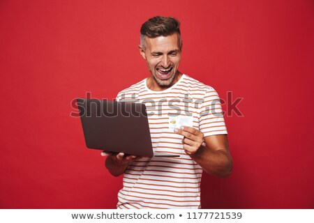 image of bearded man in striped t shirt smiling while holding cr stock photo © deandrobot
