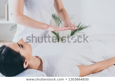 young woman receiving reiki treatment by therapist stock photo © andreypopov