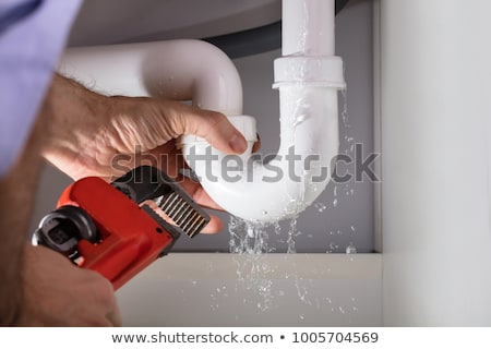 Male Plumber Fixing Faucet In Kitchen Stock photo © AndreyPopov