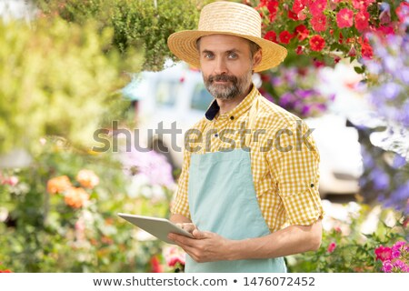 bearded mature man in apron and hat scrolling in touchpad stock photo © pressmaster