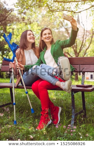 Woman and her friend with a sprained ankle taking a photo Stock photo © Kzenon
