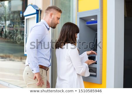 Photo stock: Man Spying For Pin Code While Woman Using An Atm