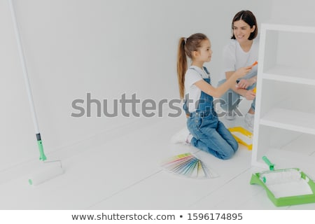 Busy girl and her smiling mother paint drawer in white color, use paintbrush or roller, surrounded w Stock photo © vkstudio