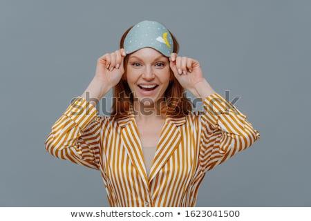 Ginger female model wears sleepmask and striped pajamas, awakes in good mood, realizes today is week Stock photo © vkstudio