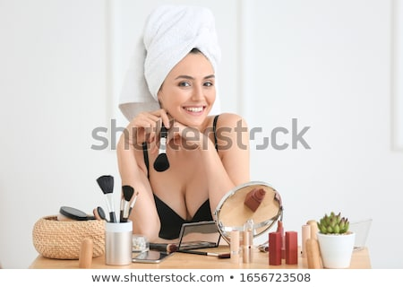 beautiful young woman applying makeup Stock photo © dotshock