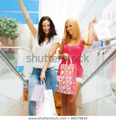 Closeup of two attractive happy girls out shopping. They are mov Stock photo © HASLOO