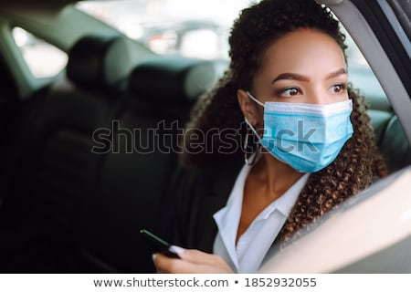 Stock photo: businesswoman in a car talking on her cell