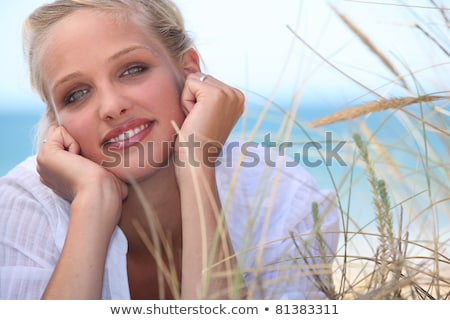 Attractive blond, laid on the beach Stock photo © photography33