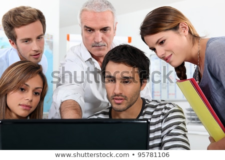 Older students and teacher gathered round a computer Stock photo © photography33