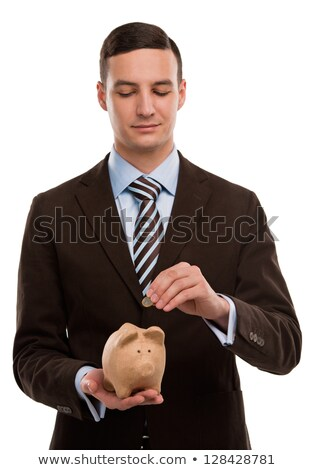 Young happy business man putting money in the piggybank over whi Stock photo © HASLOO