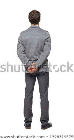 cheerful businessman with arms folded standing on gray background stock photo © deandrobot