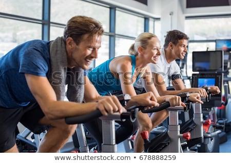 group of men and women spinning on fitness bikes in gym stock photo © kzenon