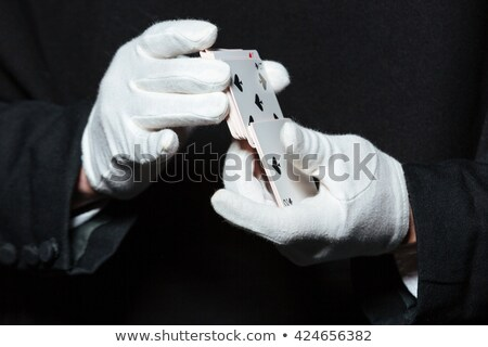 Hands of man magician in white gloves shuffling playing cards Stock photo © deandrobot