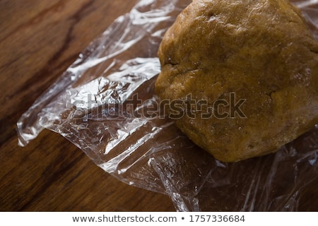 Dough placed over plastic wrap on a wooden table Stock photo © wavebreak_media