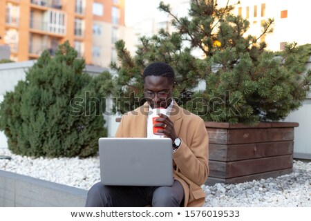 Photo of adult handsome man in businesslike suit sitting on benc Stock photo © deandrobot