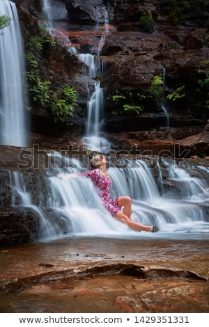 Exhilaration in mountain waterfall, female sitting in flowing ca Stock photo © lovleah