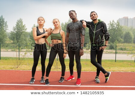 Four young friendly intercultural people in sportswear standing on racetrack Stock photo © pressmaster