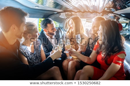 Group of women and men clinking glasses in a limousine Stock photo © Kzenon