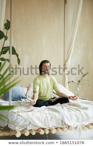 Man doing lotus pose yoga with nature plants Stock photo © cienpies