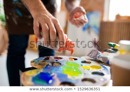 Young male painter adding gouache of orange color in palette before mixing Stock photo © pressmaster