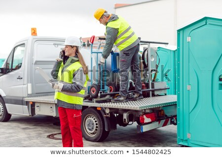 Workers taking care of a delivery of mobile rental toilets Stock photo © Kzenon
