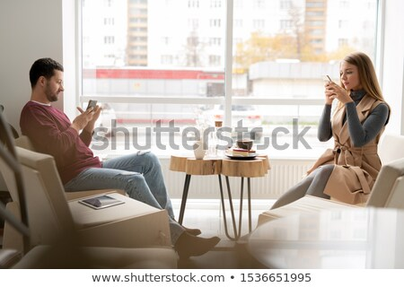 two millennials in casualwear sitting against window and scrolling in gadgets stock photo © pressmaster