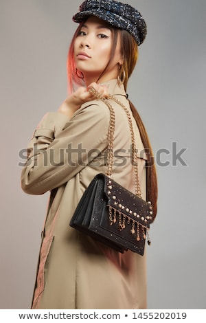 Beautiful young fashion model wearing a trench coat and sequins  Stock photo © dashapetrenko