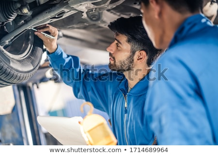 mechanic man with flashlight repairing car at shop Stock photo © dolgachov