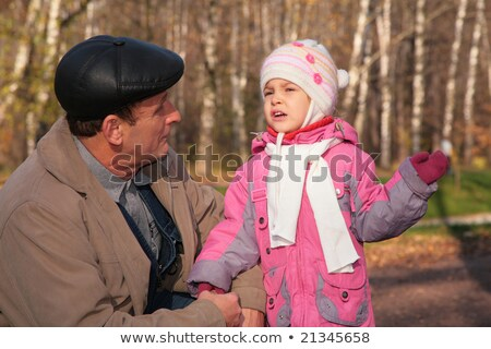 Grandfather talks  with granddaughter in wood in autumn