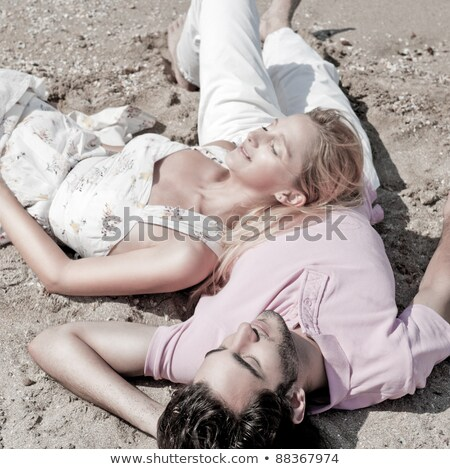 Young couple relaxing on sand at beach and daydreaming with thei stock photo © HASLOO