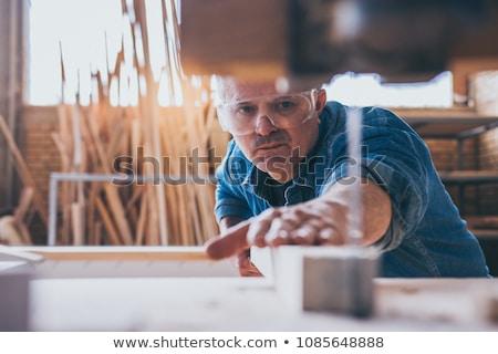 A mature carpenter sawing. Stock photo © photography33
