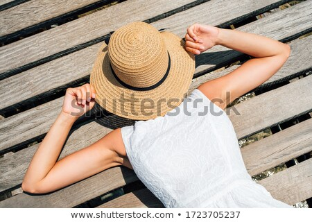Portrait of the beautiful girl on the beach hiding her eyes with Stock photo © HASLOO