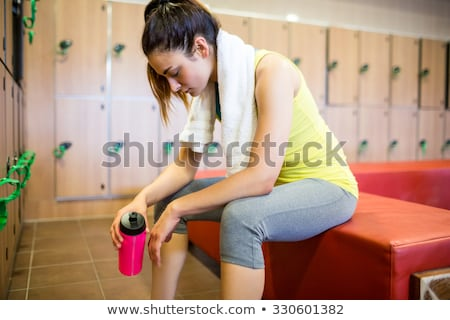 woman holding bottle at gyms locker room stock photo © candyboxphoto